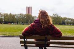 Frau, die auf Bank in einem Park stillsteht Stockfotografie