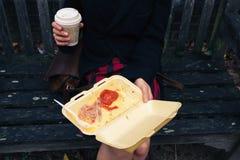 Frau, die auf Bank frühstückt Lizenzfreie Stockbilder