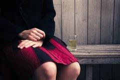 Frau, die auf Bank mit Glas Bier sitzt Stockfotos