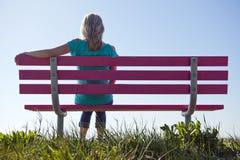 Frau, die auf Bank sitzt Stockbild