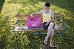 Frau, die auf Bank sitzt lizenzfreies stockfoto