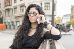 Frau, die auf Bank sitzt und telefonisch in der Straße spricht Lizenzfreie Stockfotografie