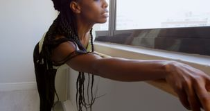 Frau, die auf Barre nahe Fenster 4k ausdehnt stock video footage