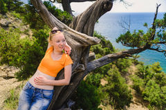 Frau, die auf Baum liegt Lizenzfreies Stockfoto
