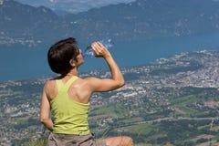 Frau, die auf Berg trinkt Stockfoto