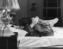 Frau, die auf Bett ausdehnt stockbilder