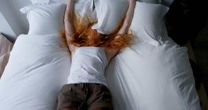 Frau, die auf Bett im Schlafzimmer 4k liegt stock video footage