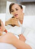 Frau, die auf Bett legt und Gesicht im Spiegel überprüft Lizenzfreie Stockfotos