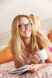 Frau, die auf Bett-Lesezeitung sich entspannt lizenzfreie stockfotos