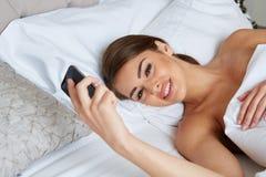 Frau, die auf Bett liegt Lizenzfreie Stockfotos