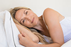 Frau, die auf Bett liegt Stockfotografie