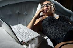 Frau, die auf Bett mit einem Laptop liegt Stockbild