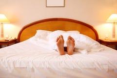 Frau, die auf Bett mit weißen Blättern sich entspannt Stockfotografie