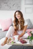 Frau, die auf Bett sitzt Stockfoto
