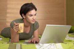 Frau, die auf Bett unter Verwendung des Laptops liegt lizenzfreie stockfotografie