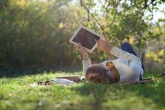 Frau, die auf Bettwäsche auf grünem Gras mit ipad liegt Stockfotografie