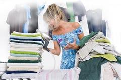 Frau, die auf Bügelbrett viel Kleidung bügelt Lizenzfreie Stockfotografie