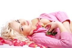 Frau, die auf Blumenblättern liegt Lizenzfreie Stockfotos