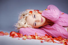 Frau, die auf Blumenblättern liegt Stockbild