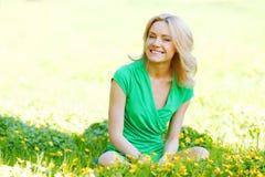 Frau, die auf Blumenfeld sitzt Stockfotos