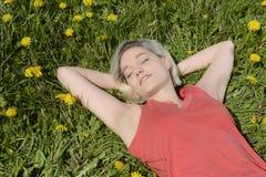 Frau, die auf Blumenwiese liegt Lizenzfreie Stockfotografie
