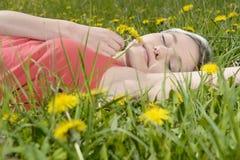 Frau, die auf Blumenwiese liegt Stockbild