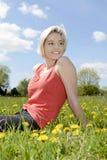 Frau, die auf Blumenwiese sitzt Lizenzfreie Stockfotos