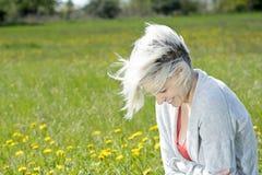 Frau, die auf Blumenwiese sitzt Stockbild