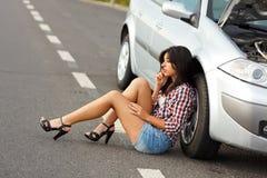 Frau, die auf Boden nahem gebrochenem Auto sitzt Lizenzfreie Stockfotos