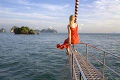 Frau, die auf Bogen der Yacht sitzt Stockbild