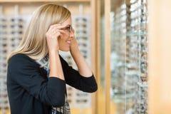 Frau, die auf Brillen im Speicher versucht lizenzfreies stockfoto