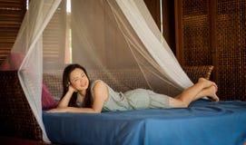 Frau, die auf Butikenbett sich entspannt stockfoto