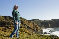 Frau, die auf Cliffside steht lizenzfreie stockfotos