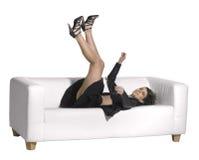 Frau, die auf Couch fällt Stockfoto