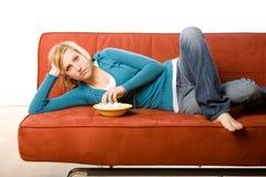 Frau, die auf Couch isst Lizenzfreie Stockfotografie
