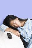 Frau, die auf Couch mit entfernter Station beiseite schläft lizenzfreies stockfoto