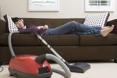 Frau, die auf Couch mit Staubsauger sich entspannt stockbilder