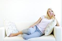 Frau, die auf Couch sich entspannt Stockfotos