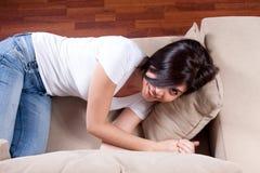 Frau, die auf Couch stillsteht Lizenzfreie Stockfotografie