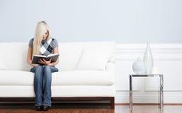 Frau, die auf Couch und Lesebuch sitzt Lizenzfreie Stockfotos