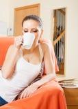 Frau, die auf Couch und trinkendem Kaffee liegt Stockbilder