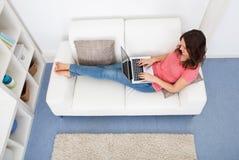 Frau, die auf Couch unter Verwendung des Laptops sitzt Stockfotos