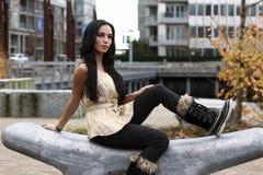 Frau, die auf curvy geschnitzter Steinbank sitzt Lizenzfreie Stockfotos