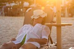 Frau, die auf das Sunbed legt und auf dem Strand schläft Lizenzfreies Stockfoto