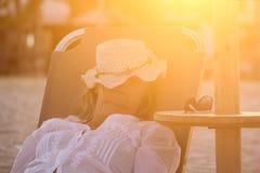 Frau, die auf das Sunbed legt und auf dem Strand schläft Lizenzfreie Stockfotografie