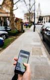 Frau, die auf das uber Auto auf der Straße hält Smartphone wartet Stockfotografie