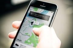 Frau, die auf das uber Auto auf der Straße hält Smartphone wartet Lizenzfreie Stockfotografie