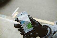 Frau, die auf das uber Auto auf der Straße hält Smartphone wartet Stockfoto
