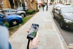 Frau, die auf das uber Auto auf der Straße hält Smartphone wartet Lizenzfreies Stockbild