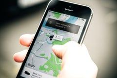 Frau, die auf das uber Auto auf der Straße hält Smartphone wartet Stockbild